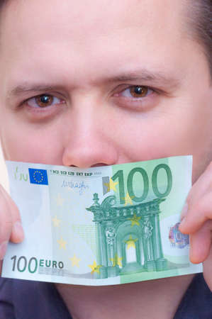 Close-up portrait of young Caucasian Ethnicity man covering mouth with money banknote one hundred euro Reklamní fotografie