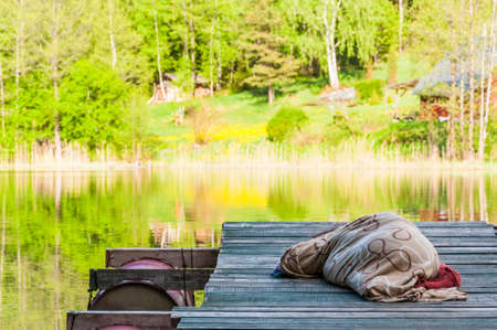Amazing lake in the middle of emerald forest. Adult is sleeping on wooden pier covered with plaid. Waterscape dreaming in Lithuania.