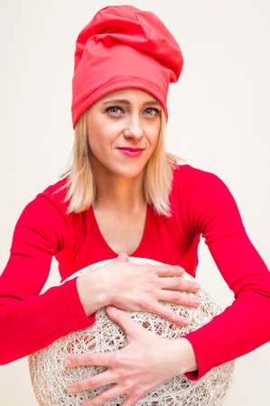 Red hat and dress smiling blonde woman embraces huge white wicker ball portrait on white background. Zdjęcie Seryjne