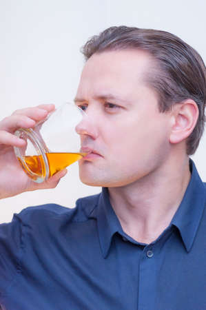 Portrait of young Caucasian Ethnicity man with blue shirt drinking whiskey brandy on white background.