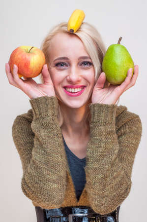 People with fruits and vegetables. Healthy lifestyle. Young smiling woman showing apple pear and banana on her head.