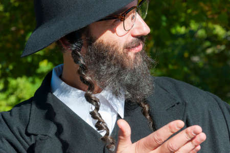 Outdoor sunny portrait of a young happy praying traditional orthodox Jewish man with eyeglasses and black beard, hat and costume Stok Fotoğraf - 113221079