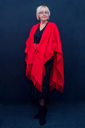 Portrait of standing attractive blonde mature woman with big red shawl