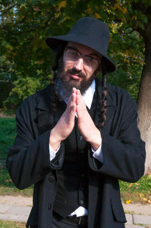 Sunny outdoor portrait of a young smiling happy fingers blessing traditional orthodox Jewish man with black beard and hat wearing eyeglasses