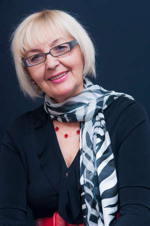 Portrait of sitting smiling attractive blonde mature woman with eyeglasses and black and white scarf Foto de archivo