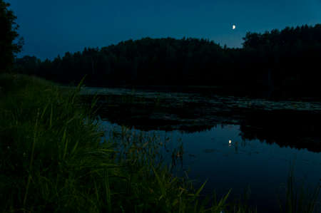 Night waterscape on lake coast with sky moon and forest reflection on water surface. Low light scenery.