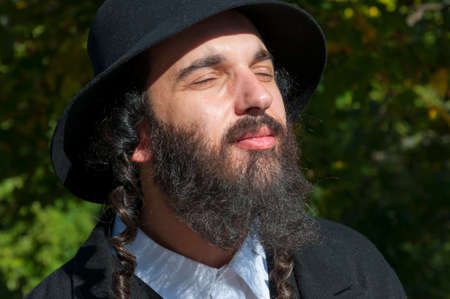 Outdoor sunny bright portrait of a young traditional orthodox Jewish man with eyes closed with black beard, hat and costume Stock Photo