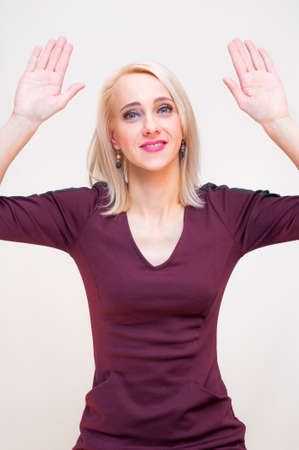 Young smiling blonde woman showing raised arms hands up sign on white background. Stock Photo