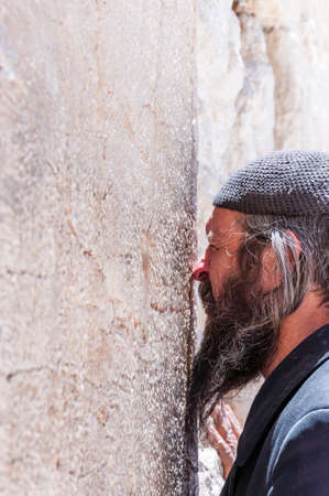 Jerusalem, Israel - April 29, 2014: Jewish Orthodox man praying with a lot of energy and strong emotions near the stones of the Western Wall. Western Wall is one of the major ancient Jewish relics.