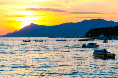 Sunset motorboats on the Adriatic sea beach in Makarska, Croatia