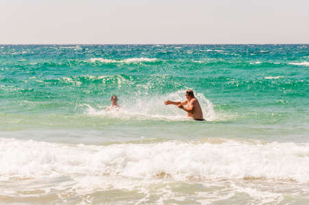 Here you can see a two young men play in the water, pour each other in the Mediterranean Sea.