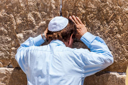Jerusalem, Israel: Secular Jewish man praying near the stones of the Western Wall full of written notes to God. Western Wall is one of the major ancient Jewish relics.