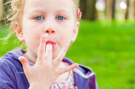 The photograph shows blue-eyed blonde girl that sucking candy-floss fingers one after another and making it with love and inherent to children passion. Stok Fotoğraf