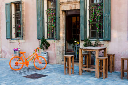 Jaffa, Israel: Old Jaffa building with orange painted bike, wooden bar tables and stools, metal barrels with plants and flowers. 版權商用圖片