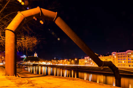 Vilnius, Lithuania. Night cityscape view of the Neris River, the sculpture Quay arch, the Mindaugas Bridge, the Old Town coastline and the Gediminas Tower