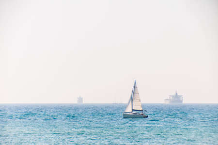 Sailing Yachts and Sea Cargo Container Ships in Mediterranean Sea waters.