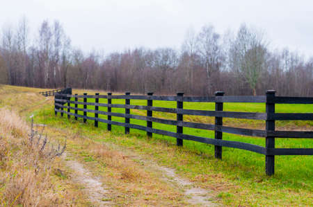 Fall time in country. Here you can see the wooden fence boundary surrounding still green grass field and rural walking path beside the fence.