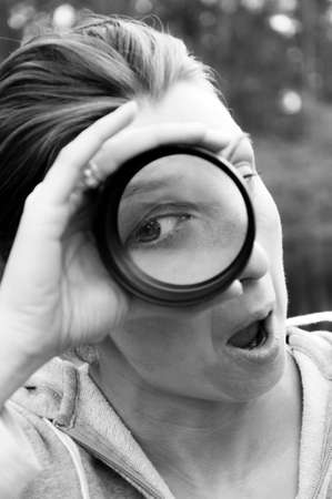 Woman looking with one eye through the magnifying lens. Disproportion is obvious and interesting in some ways.