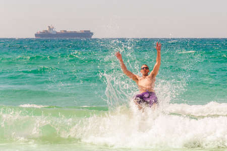 Here you can see a young man with sunglasses during the back jump to the waves of the Mediterranean Sea and huge container ship on the horizon.