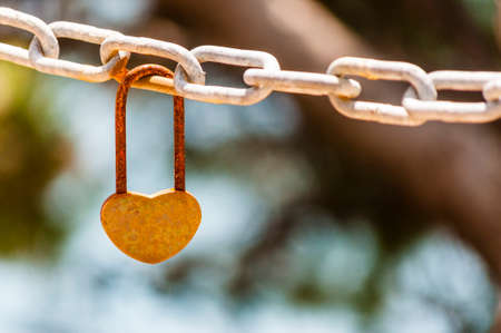 Heart shape rusty love lock hanging on a metal chain