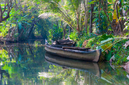 Traditional boat of Kerala Backwaters moored to the shore. Backwaters in Kerala is a network of 1500 km of canals both man made and natural. Stock Photo