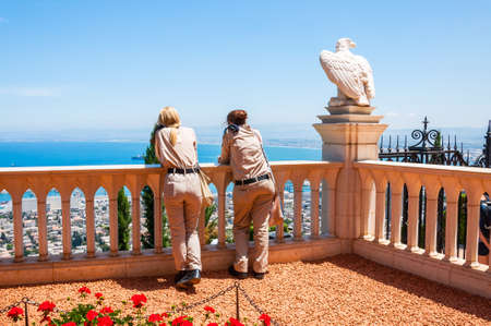 Haifa, Israel - May 22, 2012: Two Israel army soldiers girls standing and looking on Haifa cityscape from Bahai Gardens panoramic point