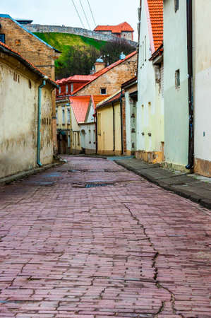 Iron manholes lying on grungy but stylish and cozy Old Town street in Vilnius. Classical European architecture street design