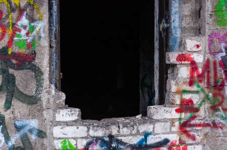 Vilnius, Lithuania - April 28, 2013: Entrance to abandoned concrete bunker built during the Second World War right in a hill near the center of Vilnius. Walls painted and decorated with graffiti