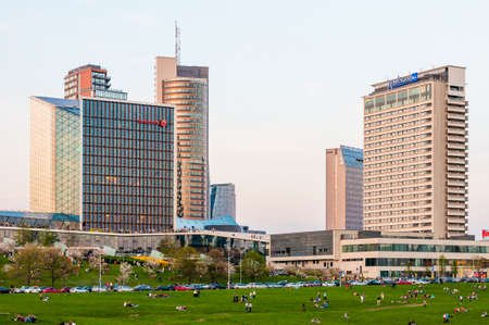 Vilnius, Lithuania - May 08, 2013: Vilnius downtown architecture, business district cityscape view, modern skyscrapers, hotels and shopping centers. People resting on social public park on the beach