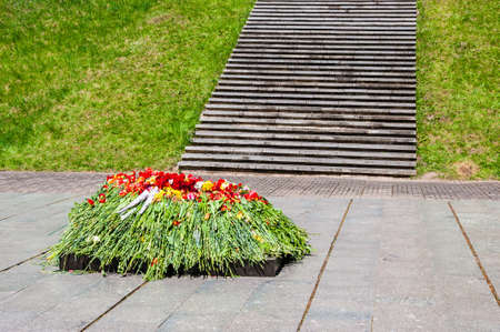 Bunch of vibrant flowers laying down near the eternal flame monument on military cemetery in honor of the day of victory in the world war two on the ninth of May each year in Vilnius