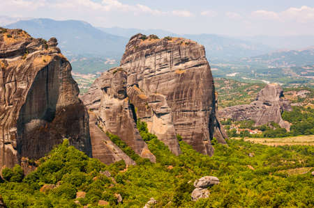Scenic landscape view on Meteora rock formations cliffs and peaks surrounded by vibrant green flora, plants and trees in Greece Standard-Bild