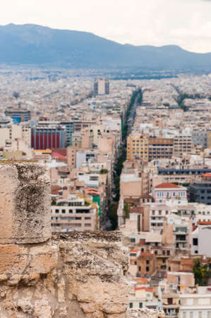 Panoramic cityscape view on Greece capital Athens city from Acropolis hill. View through ancient ruined stones on straight street