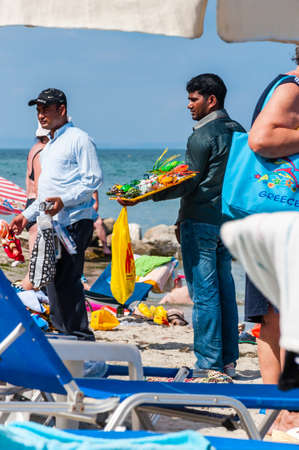 Paralia, Greece - June 14, 2013: Men holding showing offering selling various toys, sunglasses, souvenirs while walking on the beach between resting tourists. Seasonal beach resorts businesses