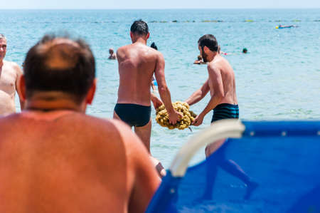 Paralia, Greece - June 14, 2013: Tourists two men found a lying down on the sand big yellow coral thrown from the Aegean sea and talking it back to the sea, trying to save it