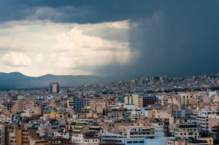 Contrast dark wall of falling water from the moody sky of the coming storm on the city. Panoramic cityscape view on Greece capital Athens city from Acropolis hill.
