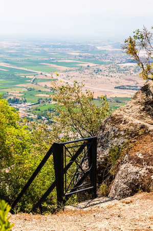 Black metal gate, railings and stairs down the hill from Meteora rock formations cliffs and peaks with scenic view on the valley full of agricultural fields near the Kalambaka town in Greece Standard-Bild
