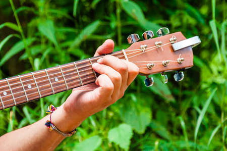 Mans hand holding chord E on a wooden acoustic guitar neck fingerboard fretboard on scenic green flora background
