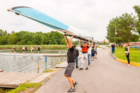 Trakai, Lithuania - July 26, 2013: Eight people carrying an eight that is a rowing boat used in the sport of competitive rowing. This summer touristic attraction is very popular in Trakai, Lithuania