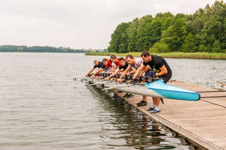 Trakai, Lithuania - July 26, 2013: Eight people holding an eight that is a rowing boat used in the sport of competitive rowing. This summer touristic attraction is very popular in Trakai, Lithuania Editorial