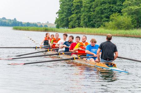 Trakai, Litauen - 26. Juli 2013: Ausbildertrainer, der Touristen unterrichtet, wie das Ruderboot acht im Wasser von Galve See arbeitet. Eight ist ein Ruderboot, das im Wettkampfrudersport verwendet wird.