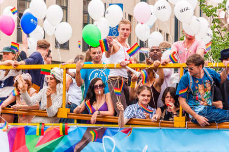 Vilnius, Lithuania - July 27, 2013: Pride parade event in action. Proud and happy people demonstrators standing on yellow open top bus decorated with vibrant and colorful rainbow flags and balloons Editorial