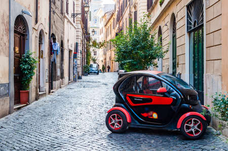 Rome, Italy - November 18, 2018: People walking by the ancient medieval Old Town paving stone street in Rome with compact red black Renault Twizy TKardinal parked on a side of the street Editorial