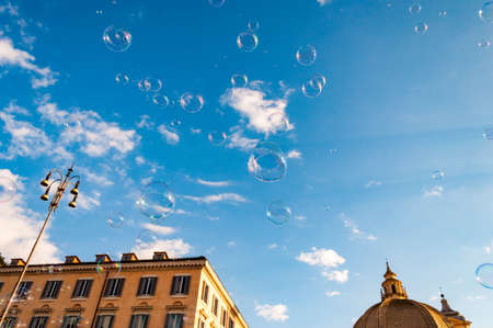 Rome, Italy: Soap bubbles flying on Piazza del Popolo, People Square in Rome surrounded by ancient churches like Santa Maria in Montesanto with its great domes and bell towers