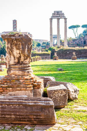Rome, Italy: View on the Temple of Castor and Pollux through the ancient remains and ruins in Roman Forum in Rome
