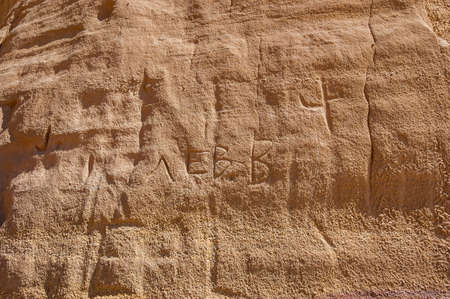 Contemporary carring sign of someone named Levv on the rock in the desert, Timna national park in Aravah valley in Israel