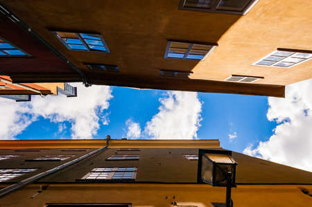 View from below on the roofs of a cozy narrow medieval street yellow orange red buildings facades in Gamla stan, Old Town of Stockholm, Sweden with bright blue sky on the background