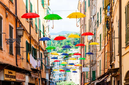 Sanremo, Italy - September 01, 2019: Vibrant colorful umbrellas hanging on cables fixed high on building facades