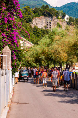 Monterosso Al Mare, Italy - September 02, 2019: People walking by the seafront promenade decorated with blooming Bougainvillea flowers evergreen trees in famous Monterosso Al Mare, Cinque Terre, Italy