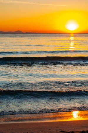 The sunset sun is going down behind the horizon. Tyrrhenian Sea bay with Elba island on the background at the sunset. Cala Violina beach, Scarlino, Province of Grosetto, Italy