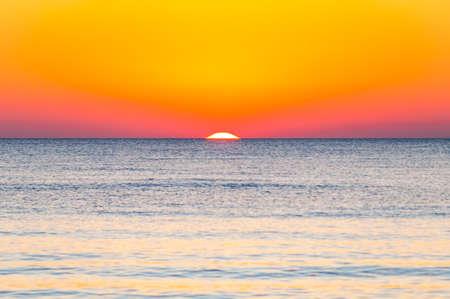The last seconds of the amazing sundown behind the sea horizon. A bit of the sun star sphere showing up above the Tyrrhenian sea level. Vibrant sunset on Cala Violina beach, Scarlino, Grosetto, Italy
